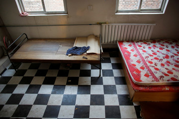 Beds are seen in a room that used to be inhabited by migrant workers in a low-cost dormitory that has been cut off from water and electricity supply in Beijing