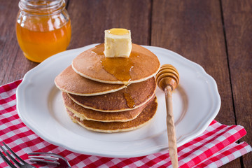 stack of pancakes with butter and honey on a white plate and a wooden background