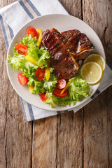 Delicious grilled T-bone steak with fresh vegetable and lemon close-up. Vertical top view