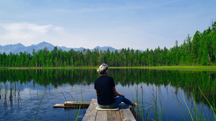 Lonely dreaming woman sitting on a wooden bridge pier looking at the mountains reflected in the mirror water of the forest lake. Serenity concept. Pure nature.