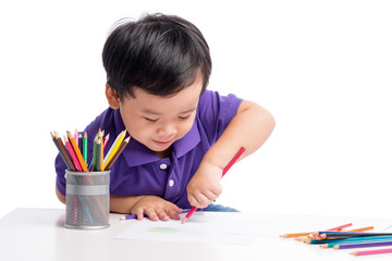 Portrait of cheerful boy drawing with colorful pencils