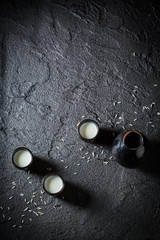 White sake in black ceramics on black rock