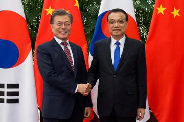 South Korean President Moon Jae-In shakes hands with China's Premier Li Keqiang in Beijing