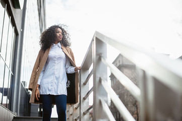 Portrait of a beautiful natural young African woman with afro, outdoor fashion portrait in sun