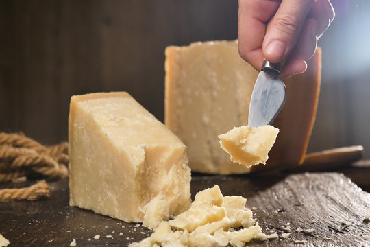 macro of a middle aged chef cutting cheese with knife on wooden board on restaurant kitchen table (extra close up)