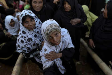 Rohingya refugees queue to receive food at the Kutupalong refugee camp near Cox's Bazar