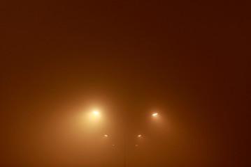 Street lights shine through evening fog covering Skopje