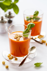 Glass with delicious homemade cream tomato soup with croutons. Healthy food concept.