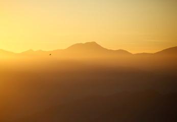Light illuminates the mountain range and hills during the sunrise over the Nagarkot valley