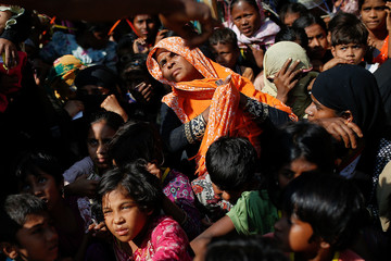 Rohingya refugees wait for a food distribution at the Balukhali refugee camp near Cox's Bazar