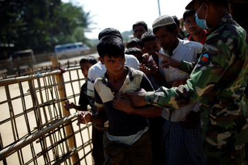 A Bangladeshi soldier tries to organise Rohingya refugees in a queue during food distribution at the Balukhali refugee camp near Cox's Bazar