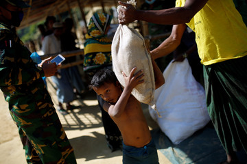 Rohingya refugee is given food supplies during distribution at the Balukhali refugee camp near Cox's Bazar
