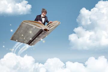 Mann fliegt auf einem Buch über den Wolken