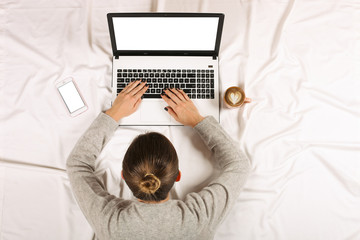 Young woman tired and fall asleep in front of her laptop at home in the bed top view