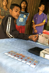 A public health worker takes a blood sample from a woman to be tested for malaria  in Bo Rai district, Trat provice