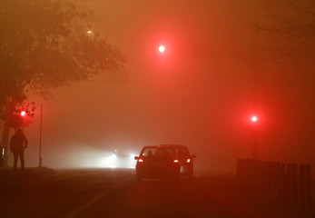 Vehicle traffic and pedestrians are seen during evening fog and air pollution covering Skopje