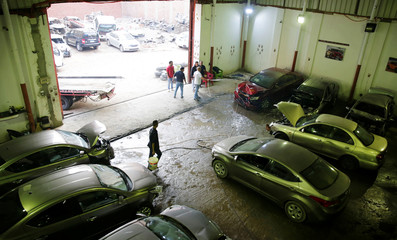 Employees work on new arrival of cars at the workshop of El Faqyier (The Poor), a crash-damaged vehicles and second-hand car shop, in Cairo