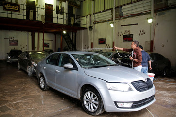 An employee works on a car, at the workshop of El Fauquier (The Poor), crash-damaged vehicles and second-hand car shop in Cairo