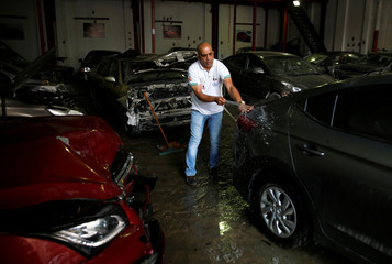 Mohamed Shaheen, owner of El Faqyier (The Poor), a crash-damaged vehicles and second-hand car shop, washes a new arrival car in Cairo