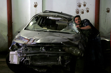 An employee works on a car, at the workshop of El Fauquier (The Poor), a crash-damaged vehicles and second-hand car shop in Cairo