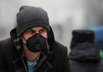 Man walks wearing an anti-particle mask, to protect myself from air pollution in Skopje