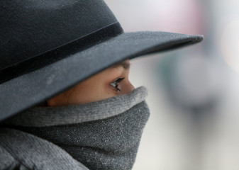 Woman walks with a covered face to protect herself from air pollution in Skopje