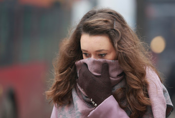 Woman covers her face during a period of fog and air pollution in Skopje