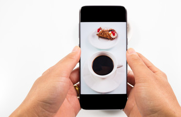 Close-up image. hands using smartphone to take a photo or look a picture of coffee and sweet dessert in white background.