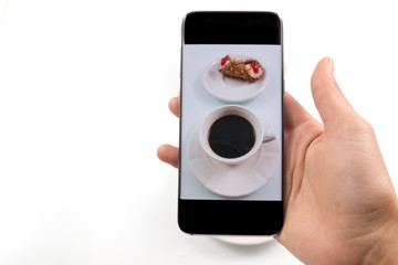 Close-up image. hands using smartphone to take a photo of coffee and sweet dessert in white background.