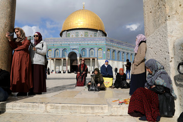 """Worshippers sit around before Friday prayers on the compound known to Muslims as Noble Sanctuary and to Jews as Temple Mount in Jerusalem's Old City, as Palestinians call for a """"Day of Rage\"""
