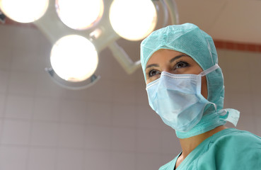 A young woman poses  in an operation theater  fully dressed as a theater nurse with a face mask  and green sterile medical work clothing.