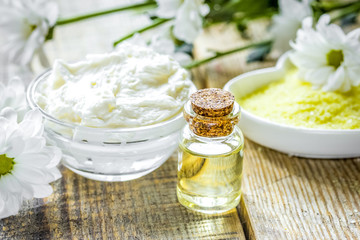 homemade cosmetics with camomile herbs on wooden background