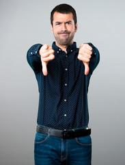 Handsome man making bad signal on grey background