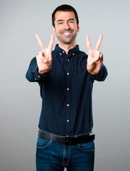 Handsome man making victory gesture on grey background
