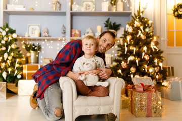 New Year's picture of dad hugging son sitting on chair