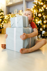 New Year's picture of boy with gift box on background of Christmas decorations