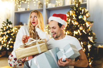 Picture of cheerful couple in Santa cap with gift in box