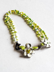 bracelet with a clasp in the form of white flowers with enamel.