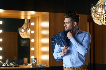 Sexy man model staying near the mirror and looking away