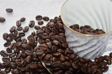 Roasted coffee beans and decorative teacup on a light background