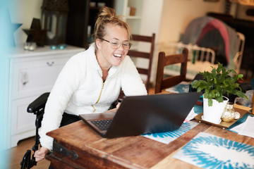 Smiling disabled woman using laptop at table in house