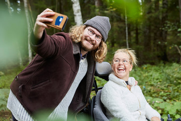 Couple taking selfies in forest