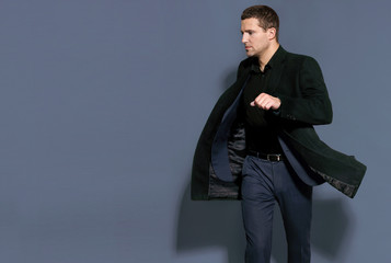 man in a black coat on a gray background studio
