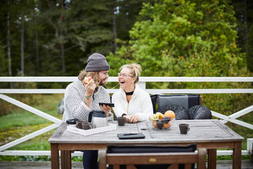 Male caretaker and disabled woman listening to music on smart phone at table in yard