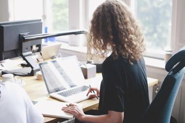 Rear view of young businesswoman using laptop at table in creative office