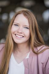 Portrait of smiling blond girl standing at parking garage