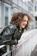 Smiling teenage boy leaning on railing in city