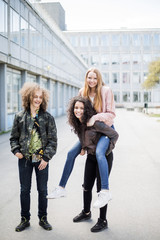 Teenage boy standing by girl giving piggyback to friend