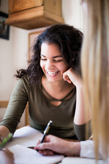 Smiling teenage girl doing homework with female friend at home