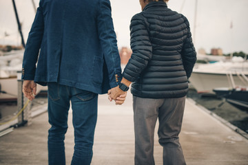 Midsection of senior couple holding hands while walking on pier at harbor